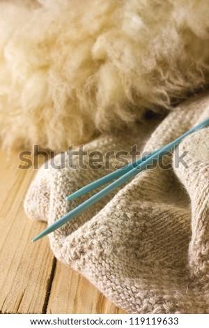 lambs wool, sheep, knitting needles on a wooden board - stock photo