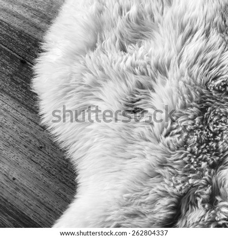 Lambs wool sheepskin on a timber floor in black and white - stock photo
