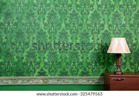 Lamp in vintage green interior with rococo pattern wall - stock photo
