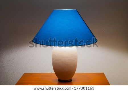 Lamp on a nightstand with a blue glow on a textured wall-diffused lighting - stock photo