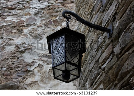 Lamp on a stone wall - stock photo