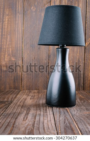 Lamp on wood background - vintage effect style - stock photo