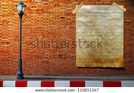 Lamp post street and old paper signboard on brick wall - stock photo