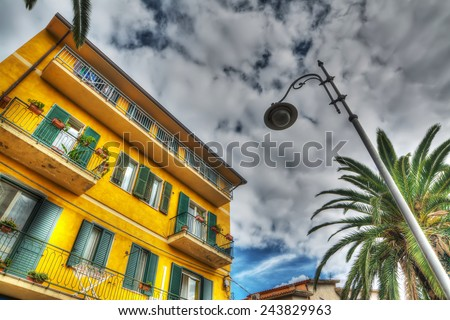 lamppost and colorful building under a gray, dramatic sky - stock photo