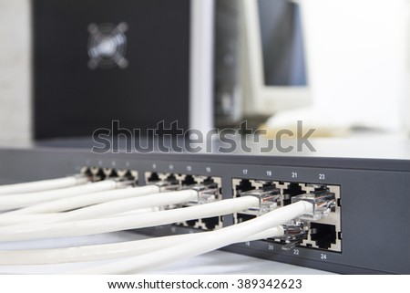 Lan network switch with ethernet cables plugged in on computer background - stock photo