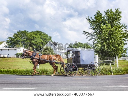 LANCASTER, USA - JULY 13, 2010: amish people ride in their horse carts in Lancaster, USA. Amish people don't use electricity as well as cars. They life the traditional way of the 17th century. - stock photo