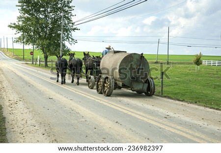 LANCASTER, USA - OCTOBER 22;: Amish horse drawn tank being pulled along a country road through farmland on October 22, 2014 in Lancaster, USA. - stock photo