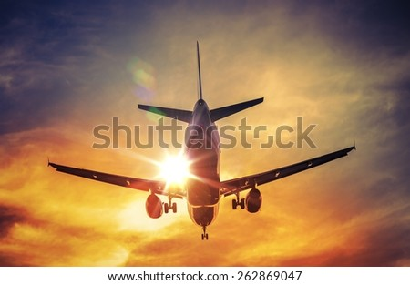 Landing Airplane and the Sun. Air Travel and Transportation Photography Concept. - stock photo