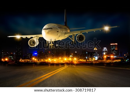 Landing business airplane to the airport runway in the night scene cityscape background - stock photo
