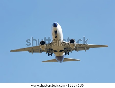 Landing commercial airplane against clear blue sky - stock photo