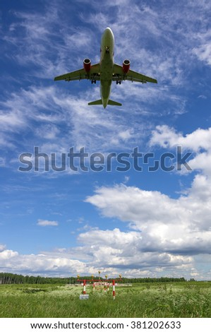 Landing jet airplane over runway approach lights - stock photo