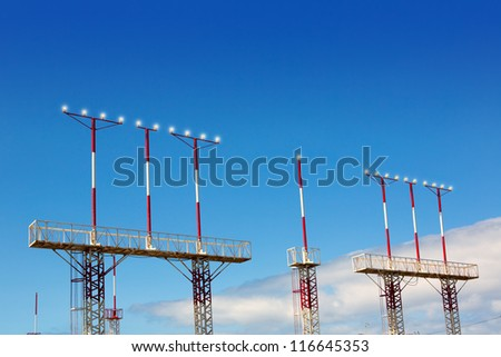 Landing lights towers in white and red over blue sky in Canary Islands - stock photo