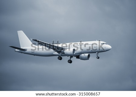 Landing of the passenger plane at sunset time. - stock photo