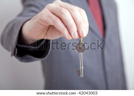 Landlord/ Realtor holding out a key to your new home - stock photo