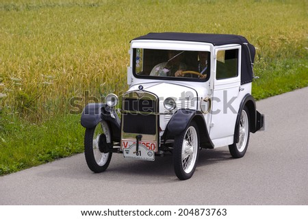 LANDSBERG, GERMANY - JULY 12, 2014: Public oldtimer rally organized by Bavarian city Landsberg for at least 80 years old veteran cars with unknown drivers in BMW Dixi, built at year 1929 - stock photo