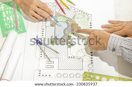 Landscape architect changing drawing at meeting with client - stock photo