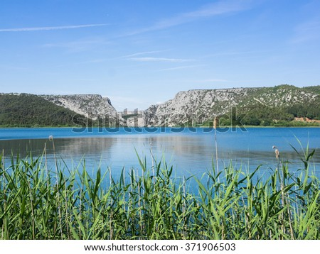 Landscape at Krka National Park in Croatia: View of river Krka with reed in the foreground and mountains in the background. - stock photo