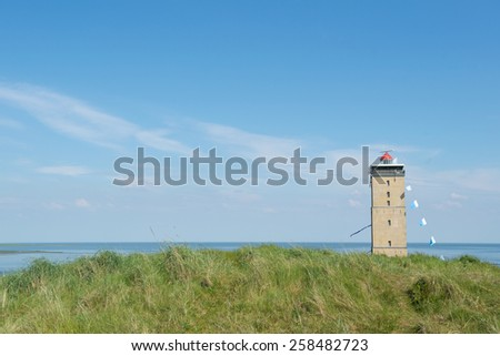 Landscape at the coast with lighthouse in Dutch Terschelling - stock photo