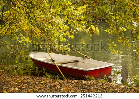 Landscape - Autumn park with red boat in the pond - stock photo
