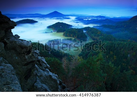 Landscape before sunrise. Cold misty foggy morning in a fall valley of Bohemian Switzerland park. Hills with fog, landscape of Czech Republic, Ceske Svacarsko national before sunrise. - stock photo