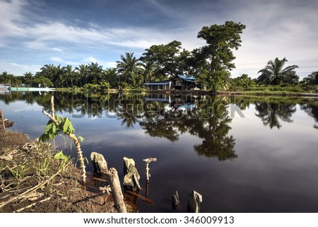 Landscape during daytime with river reflection of rural house and tree - stock photo