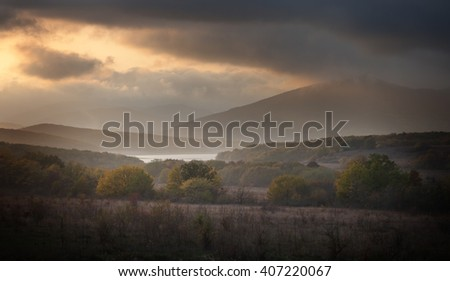 Landscape. Forest and mountains in the clouds at sunset - stock photo