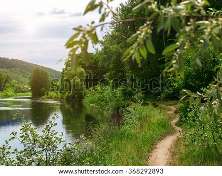 landscape - forest path along the river. Spring day on the river - sun and beautiful trees. A narrow footpath on the bank of a wide river. - stock photo
