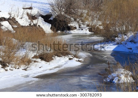 landscape frozen river near a forest in the early spring - stock photo