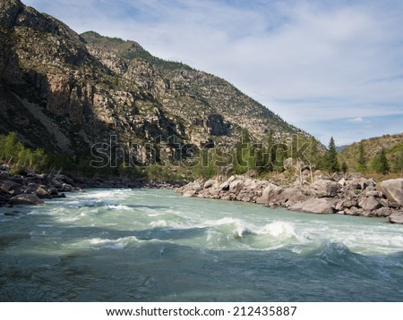 Landscape green rough river on the background of high mountains with the sky - stock photo