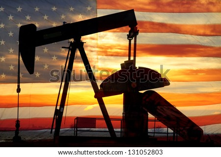 Landscape image of a oil well pumpjack wiith an early morning golden sunrise and American USA red White and Blue Flag background. - stock photo