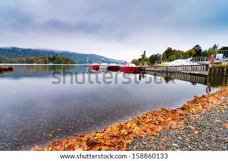 Landscape image of  Lake Windermere in Lake District, a National Park in England, during Autumn with grey sky, autumn leaves  and colourful boats next to jetty - stock photo