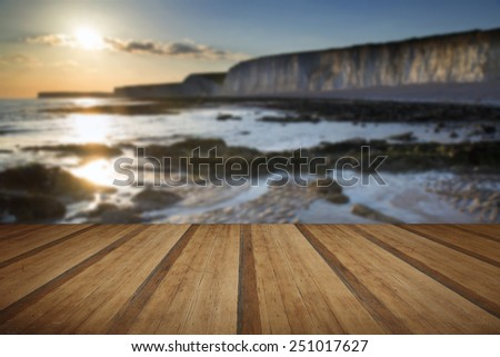 Landscape image of rocky beach at sunset with long exposure motion blur sea with wooden planks floor - stock photo