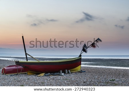 Landscape image of small fishing boats on beach at sunrise - stock photo