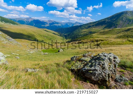 Landscape in Tarcu Mountains from Romanian Carpathian with a large rock in the foreground - stock photo