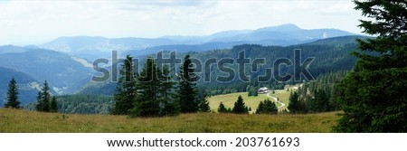 Landscape in the Black Forest; panoramic views over meadows and forests, mountains and valleys, in the background the Mountain Belchen/The Black Forest - stock photo
