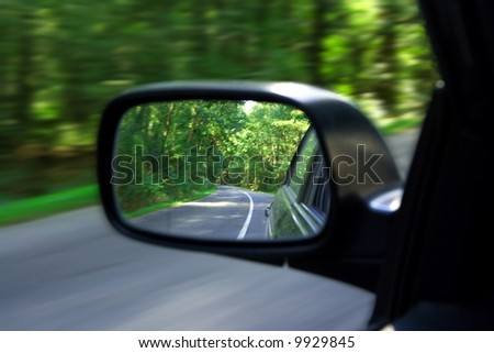 Landscape in the sideview mirror of a speeding car - stock photo