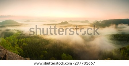 Landscape misty panorama. Fantastic dreamy sunrise on rocky mountains with view into misty valley below. Foggy clouds above forrest. View below to fairy landscape. Foggy forest hills. - stock photo