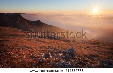 Landscape. Mountain slopes in the mist at sunrise - stock photo