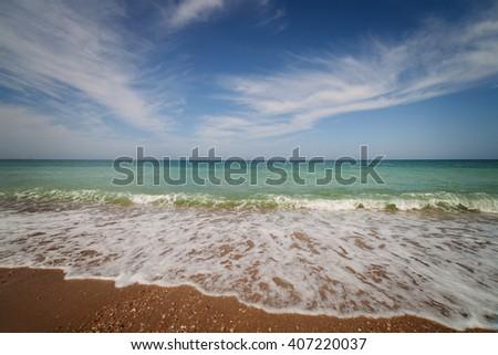 Landscape. Oceanside under blue sky with clouds - stock photo