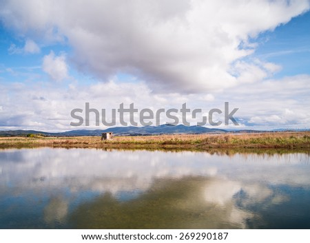 Landscape of a wetland in Tuscany with the sky that reflects itself on a lake - stock photo