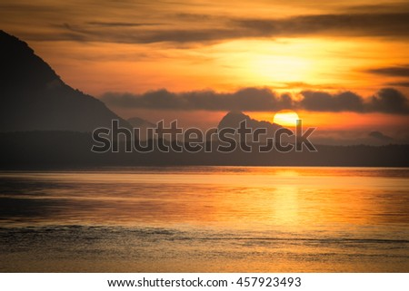 Landscape of beautiful nature sunrise at sea mountain background - stock photo
