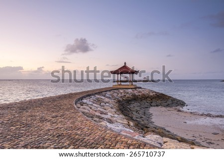 Landscape of bricks path leading to shelter at beach on a clear sky morning with puffy cloud.  Location at Sanur Beach in Bali, Indonesia. - stock photo