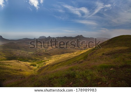 Landscape of rolling hills and valleys leading off into the distance to a range of rugged mountains under a sunny blue sky - stock photo
