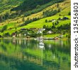 Landscape of rural town and yacht in Norwegian fjords. - stock photo