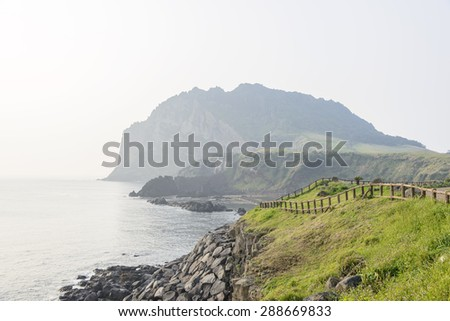 Landscape of Seongsan Ilchulbong, view from Olle trail No. 1 in a morning. Ilchulbong is a volcanic cone located on the eastern end of Jeju Island and it means the Sunrize peak. - stock photo