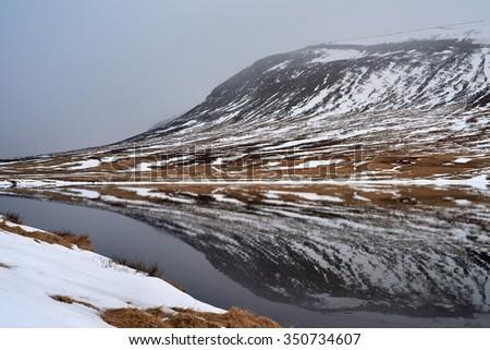 Landscape of snowy mountains reflecting in the still lake water, serene idyllic vista - stock photo