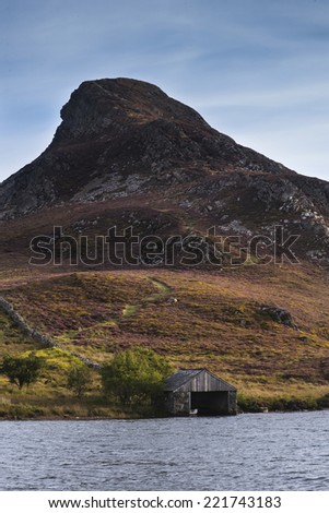 Landscape of steep hill with small boathouse on lake in foreground - stock photo