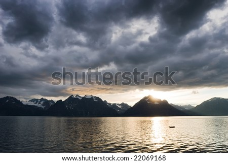 landscape of sunset with dark clouds above a lake with snow mountains coast - stock photo