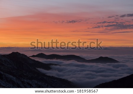 Landscape of the Sierra Nevada ski resort in Granada, Spain, with view of sky in orange, blue mountains and low clouds. - stock photo