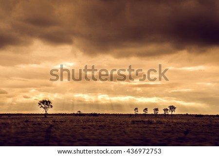 Landscape of the sun setting in outback Queensland, Australia. - stock photo